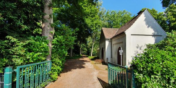 Der Eingangsbereich des Alten Friedhofs Beckhausen mit der Kapelle rechts der von Bäumen gesäumten Hauptwegeachse.