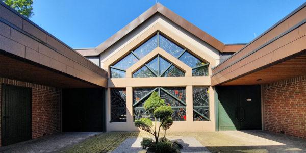 Die Trauerhalle auf dem Friedhof Beckhausen-Sutum mit einer bunten Glasfront.