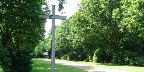 Blick auf ein Hochkreuz auf dem Friedhof Hassel-Oberfeldingen und eine Allee auf die Trauerhalle.