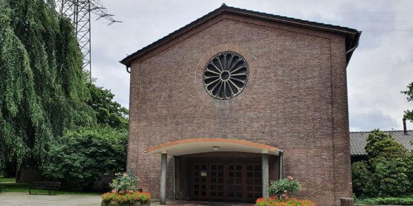 Außenansicht der Trauerhalle auf dem Ostfreidhof mit einer Backsteinfront und Glasrosette.