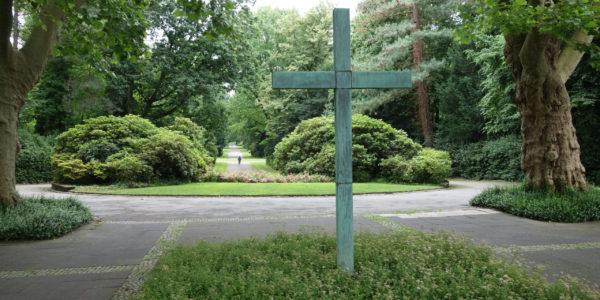 Hochkreuz im Eingangsbereich des Südfriedhofs in Ückendorf mit Blick auf die beidseitig von hohen Bäumen eingerahmte Hauptwegeachse.