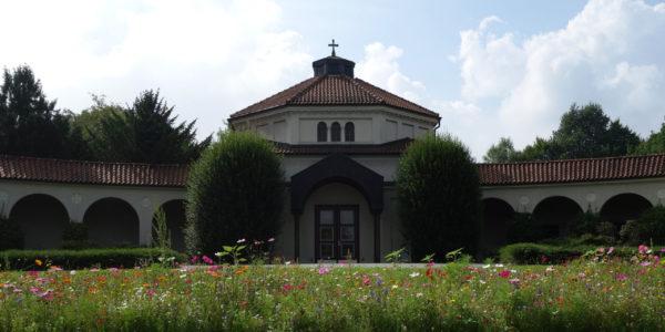 Das denkmalgeschütze Friedhofsgebäude auf dem Westfriedhof mit einer Blumenwiese im Vordergrund.